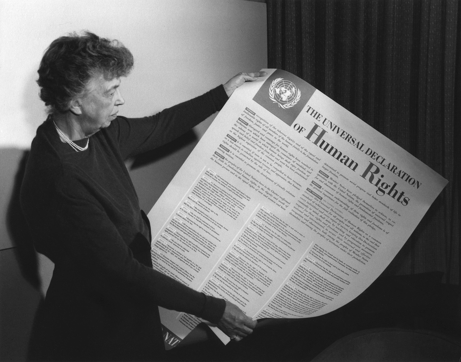 First lady Eleanor Roosevelt holding a signed copy of the United Nations declaration of Human Rights