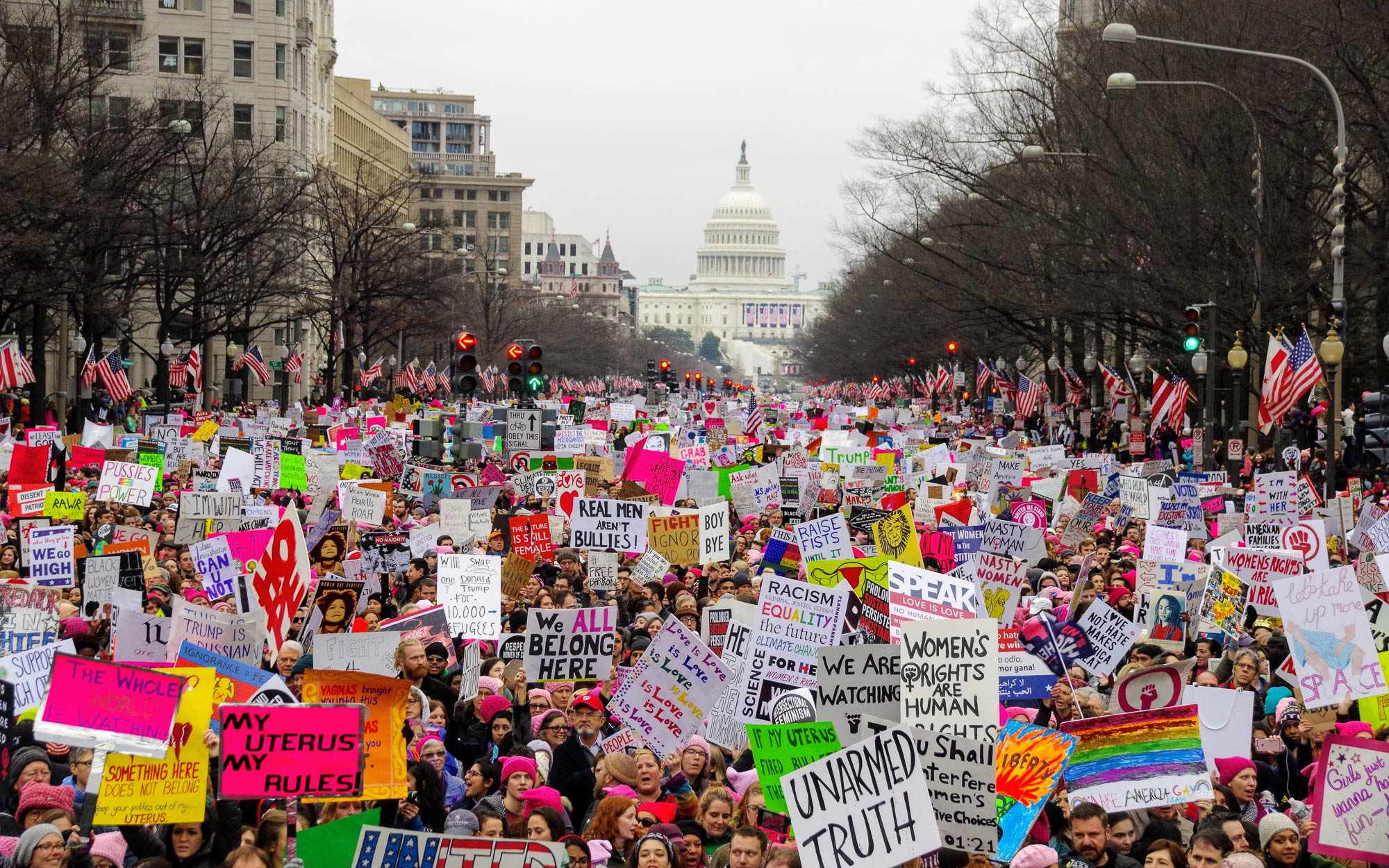 The 2017 women's march takes place in downtown Washington D.C. with the Trump Hotel and the Capitol Building in the background. Editorial credit: G. Midford / Shutterstock.com.