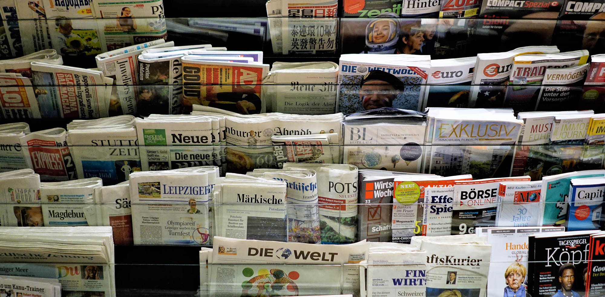 Berlin, Germany - August 2016: Colorful and interesting collection of european newspapers, periodicals, magazines in newsstand rack. Editorial credit: P Gregory / Shutterstock.com.