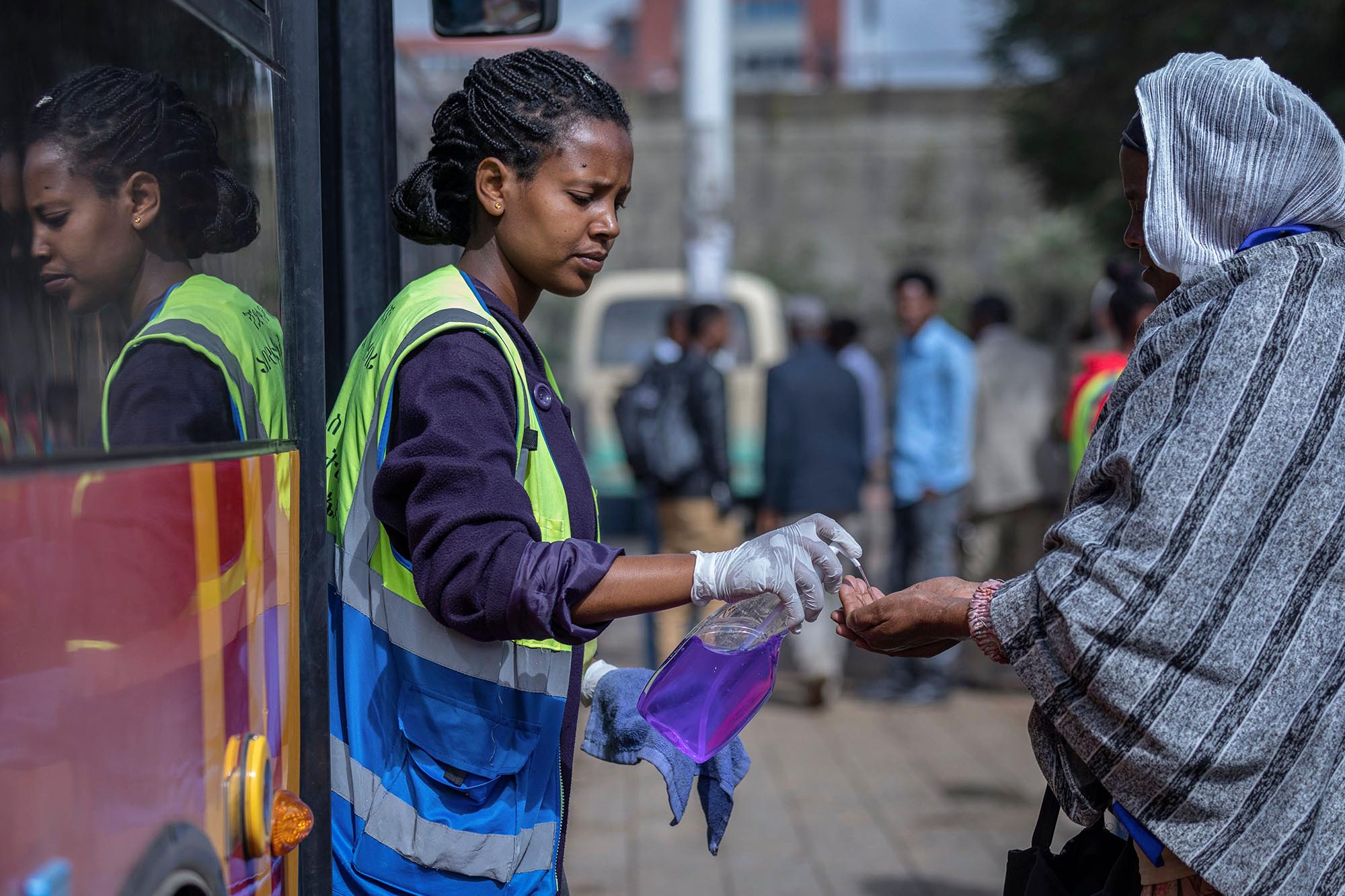 Volunteer provides hand sanitizer to passengers entering a bus as a precaution against the spread of the new coronavirus in the capital Addis Ababa, Ethiopia .