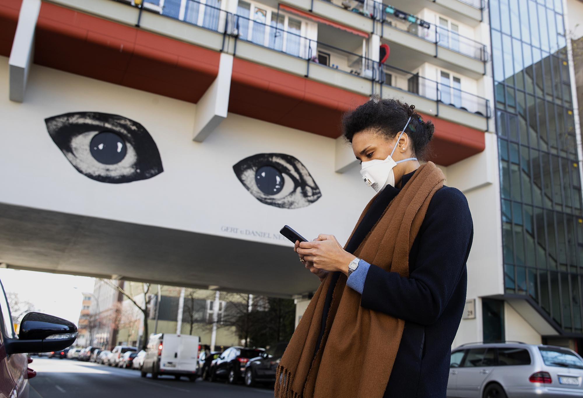 A young woman wearing a protective mask looks at her smartphone while passing by a grafitti representing two big watching eyes in Berlin, Germany on April 1, 2020. Illustrative Editorial (Photo by Emmanuele Contini/NurPhoto via Getty Images)