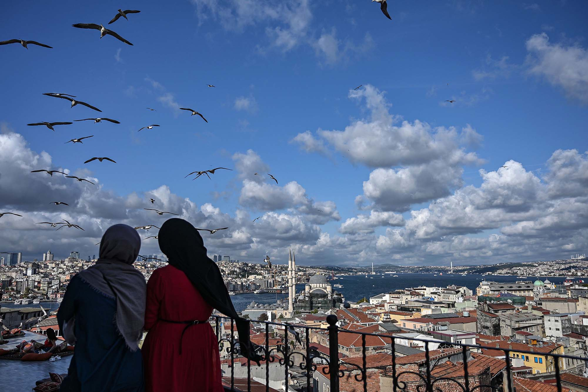 Two women look at the view from the terrace of a cafe in Istanbul as seagulls fly over them on September 10, 2019