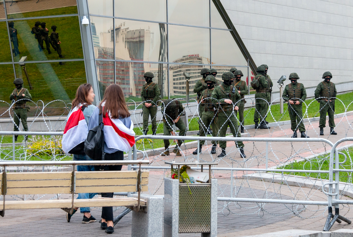 two women standing opposite of military group in Belarus