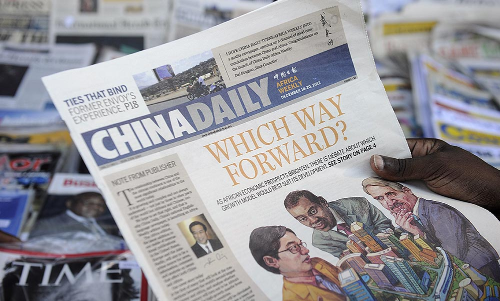 A newspaper consumer reads a copy of China's Africa edition of its daily newspaper infront of a news stand in Nairobi, Kenya.