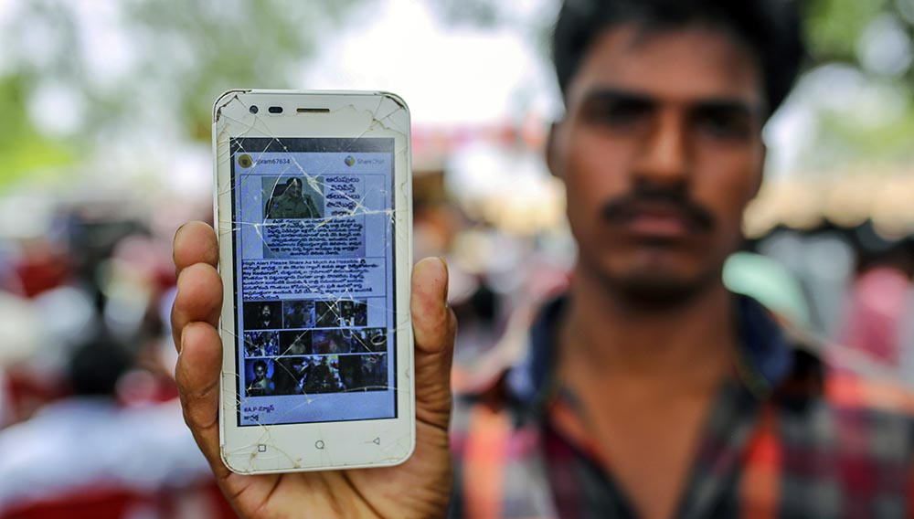 An attendee holds a mobile phone displaying a fake message shared on WhatsApp while attending an event to raise awareness of fake news in Gadwal, Telangana, India.