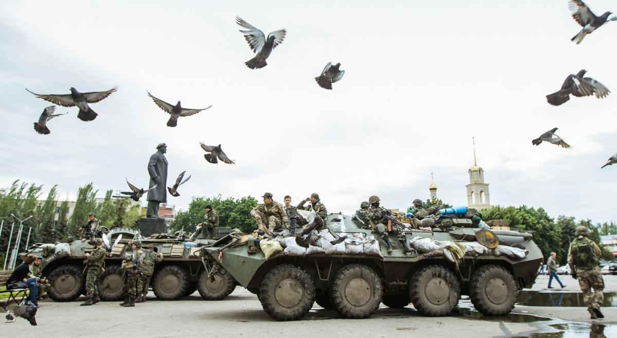 photo of a tank with soldier in Ukraine, and birds in foreground