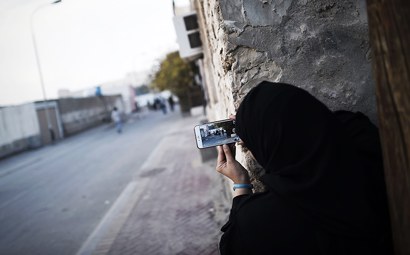 A Bahraini woman uses a mobile phone to take photos during clashes with riot police in Sitra, south of the capital Manama, January 2016. Freedomonthenet.org