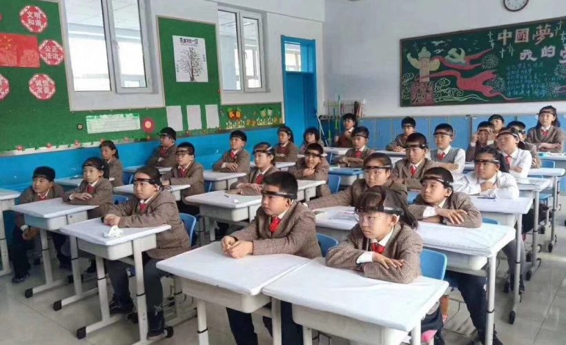 Chinese students wearing headbands sit at their desks in a classroom.