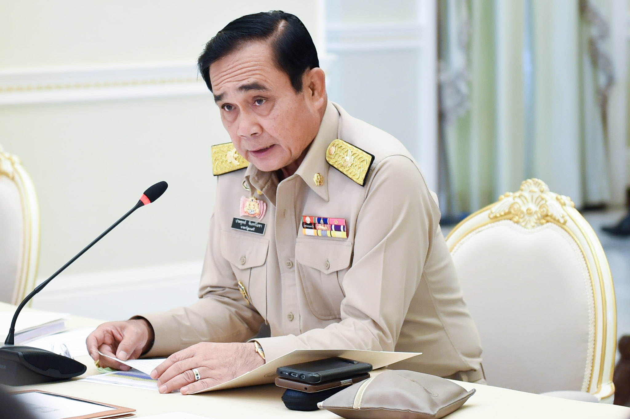 Thailand's Prime Minister Prayuth Chan-Ocha sits at a desk while speaking into a microphone.