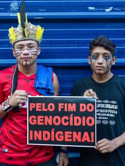 "Two young indigenous men protesting holding banner ""Stop the indigenous genocide"", in march for the rights of the indigenous people.  São Paulo, Brazil. 1 January 2019. Editorial Credit: PARALAXIS / Shutterstock.com"