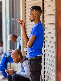 Men using their mobile phones on a sidewalk. Johannesburg, South Africa. Editorial credit:  Sunshine Seeds / Shutterstock.com