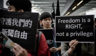 protester holds sign that says freedom is a right not a privilege hong kong china