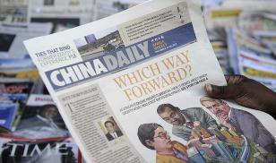A newspaper consumer reads a copy of the Africa edition of Beijing's state-run China Daily newspaper in front of a newsstand in Nairobi, Kenya. Photo Credit: TONY KARUMBA/AFP/Getty Images.