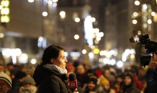 A journalist covers the scene as several hundred people rally against television propaganda in front of state outlet TVP's headquarters in Warsaw, Poland. Photo Credit: Jaap Arriens/NurPhoto via Getty Images.