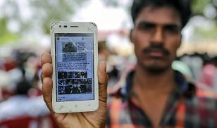 A man holds a mobile phone displaying a fake message shared on WhatsApp while attending an event to raise awareness of fake news in Gadwal, Telangana, India. Photo Credit: Dhiraj Singh/ Bloomberg via Getty Images.