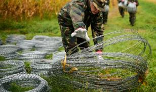 Hungarian soldiers with barbed-wire fencing on the border with Slovenia in September 2015. Photo by Jure Makovec
