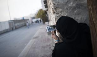 A Bahraini woman uses a mobile phone to take photos during clashes with riot police in Sitra, south of the capital Manama, January 2016. Photo credit by Mohammed al-Shaikh/AFP/Getty Images