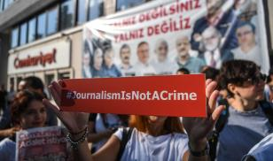 A journalist holds a banner on July 24, 2017 outside the headquarters of opposition daily newspaper Cumhuriyet in Istanbul. Editorial Credit:OZAN KOSE/AFP via Getty Images.