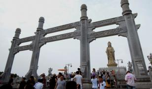 Visitors walk past the statue of a bodhisattva in a scenic park in Zhejiang Province. Credit: Kuei-min Chang
