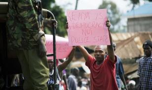 A supporter of Kenya's Opposition leader Raila Odinga shows a sign to a Kenyan policeman that reads 'Kenya is democracy not police state' during a demonstration in the street of Kisumu in 2008. Credit: YASUYOSHI CHIBA/AFP/Getty Images.