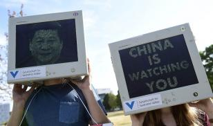 demonstrators hold desktop monitors with protest images