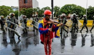 An opposition demonstrator plays the violin during a protest against President Nicolas Maduro in Caracas. Credit: FEDERICO PARRA/AFP/Getty Images.