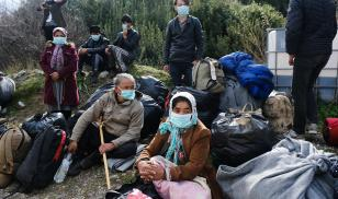Refugees wearing protective masks stand next to the military bus awaiting transfer to the port of Mytilene, Greece. coronavirus