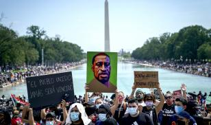 Demonstrators gather on the National Mall to protest racial injustice. An image of George Floyd is held up in front of the Washington Monument.