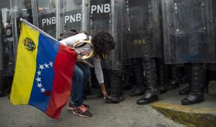 Young woman at protest facing state police in Venezuela