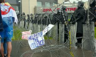 Barbed wire separates riot police from those in Minsk protesting Lukashenka. Image credit: PVLGT / Shutterstock.com