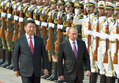 Chinese President Xi Jinping (L) and Russian President Vladimir Putin attend a welcome ceremony for Putin at the Great Hall of the People in Beijing on June 25, 2016. Editorial Credit: Kyodo News Stills via Getty Images.