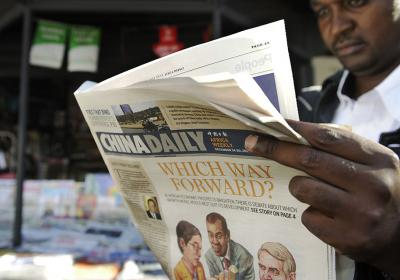 A newspaper consumer reads a copy of China's Africa edition of its daily newspaper infront of a news stand in the Kenyan capital on December 14, 2012. Photo credit:TONY KARUMBA/AFP via Getty Images.