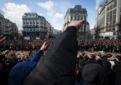 Masked and hooded men gesture outside the stock exchange in Brussels on March 27, 2016 as tensions mounted after the square was invaded by some 200 far-right football hooligans, during a tribute to the victims of the Brussels terror attacks.