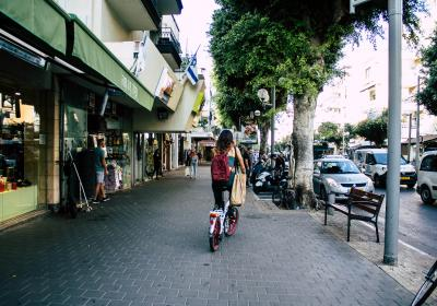 A woman commutes by bicycle through the streets of Tel Aviv, Israel. Editorial credit: Jose HERNANDEZ Camera 51 / Shutterstock.com.