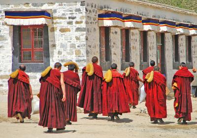 Tibetan monks outside the Labrang Monastery in Tibet. Editorial Credit: Editorial credit: Marcin Szymczak / Shutterstock.com.
