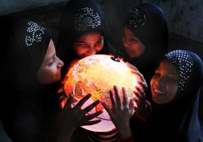 women and girls hold lit globe map of world