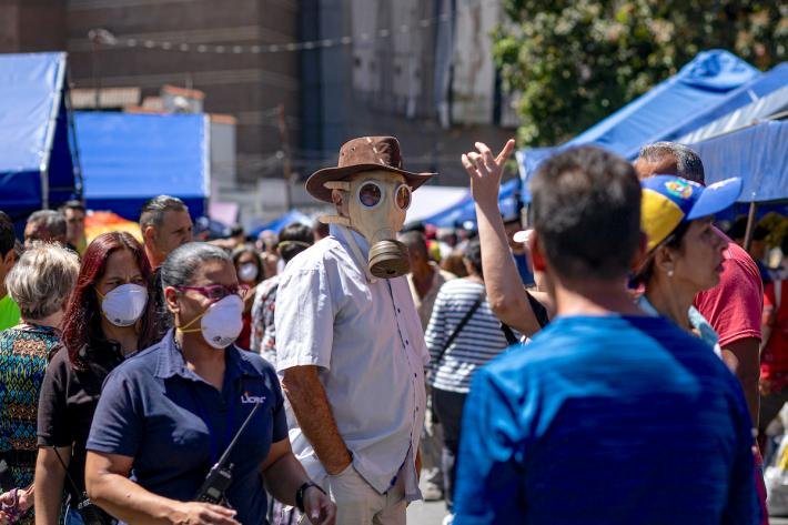 A man in a mask stands in a Caracas market. Image credit: Regulo Gomez / Shutterstock.com